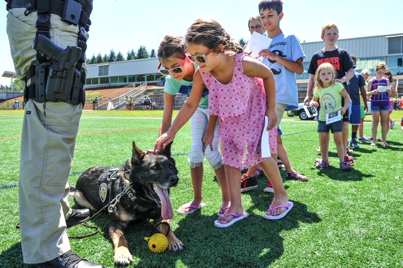 by: TIMES PHOTOS: JOHN LARIVIERE - Sharyli Mac Neil, 7, and her friend Grayce, 7, pet K-9 Officer Kahz following the Beaverton Police K-9 Unit demonstration during the Party in the Park.