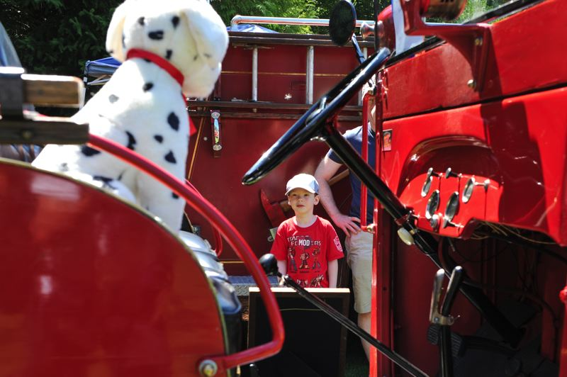 by: TIMES PHOTOS: JOHN LARIVIERE - Carlisle Strening, 6, who is visiting from Chicago, is captivated by the stuffed Dalmatian sitting on the seat of a 1931 Chevrolet Fire Truck on display at The Classic at T-Hills car show during the Party in the Park.