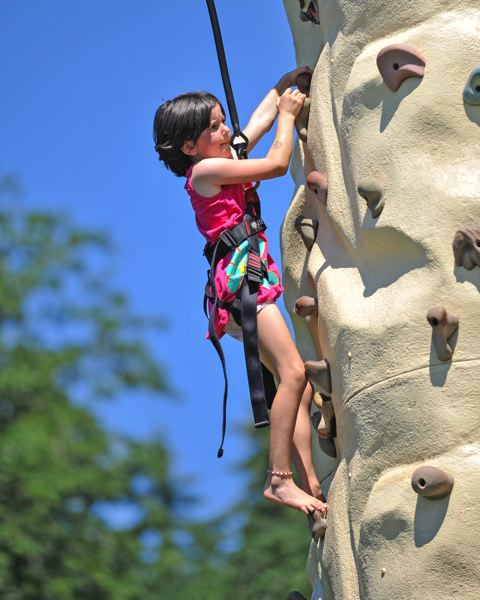 by: TIMES PHOTOS: JOHN LARIVIERE - Six-year-old Aurelia Ratten conquers the climbing wall, a popular attraction at the Party in the Park at the Howard M. Terpenning Recreation Complex.