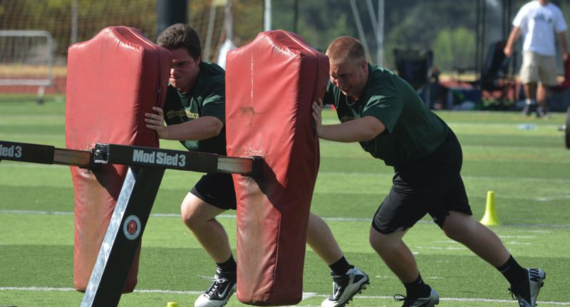 by: TIMES PHOTO: MATT SINGLEDECKER - Jesuit's Paul Vickers and Matt Woodruff push a blocking sled around at the Metro Area Linemen Challenge at Tualatin High School. Both Vickers and Woodruff are penciled in as starters up front for the Crusaders.
