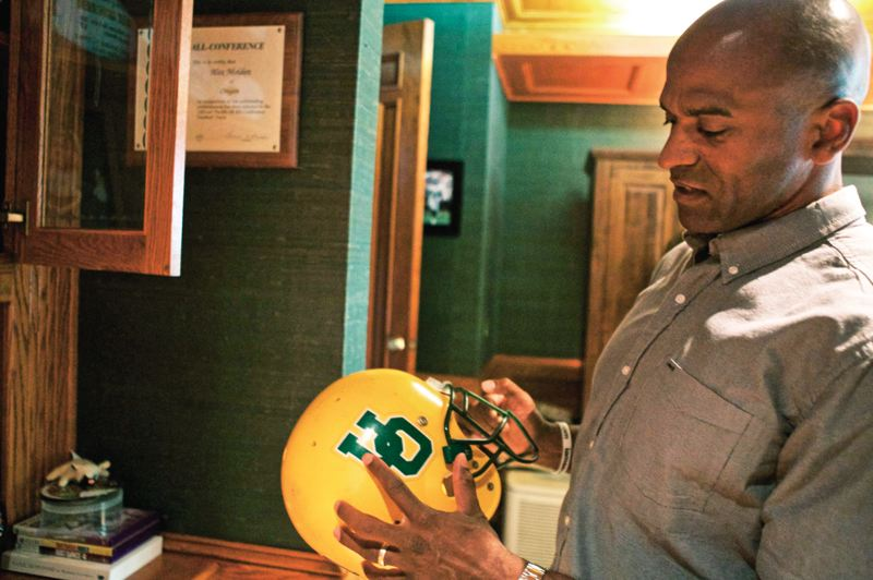 Photo Credit: TRIBUNE PHOTO: JAIME VALDEZ - Alex Molden holds the helmet he wore while playing cornerback for the Oregon Ducks from 1992-95.