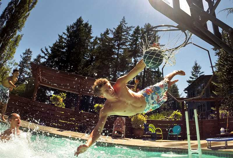 Photo Credit: TIMES PHOTO: JAIME VALDEZ - Joey Fishback jams the basketball into the hoop to complete a pool dunk at the Whitaker home in Tigard.