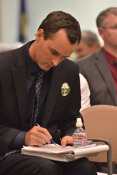 Photo Credit: REVIEW PHOTO: VERN UYETAKE - Developer Patrick Kessi takes notes before responding as opponents comments during the Development Review Commissions hearing on July 23.