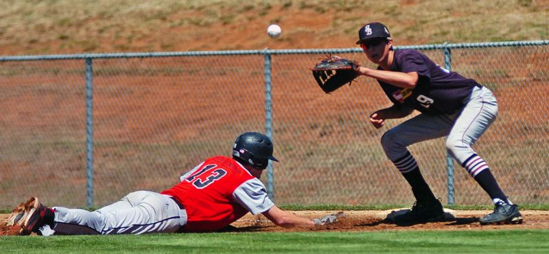Photo Credit: DAN BROOD - PICKOFF PLAY -- Sherwood first baseman Tommy Paul (right) reaches for the ball as a Clackamas runner dives back to the bag on a pickoff attempt.