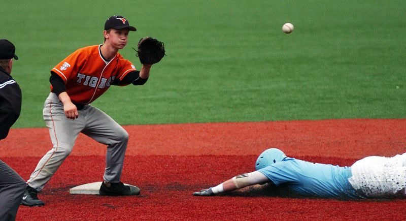Photo Credit: DAN BROOD - IN ACTION -- Tigard shortstop Cole Cameron (left) looks to grab the ball as a Lakeridge runner slides to second base in last week's OIBA tourney game.