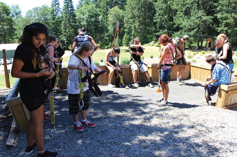 Photo Credit: HILLSBORO TRIBUNE PHOTO: KATE STRINGER - Adventure campers step into their harnesses before heading out to a zip line course of their choosing for a few hours. The three-day camp teaches kids nature survival skills in addition to zip line challenges.