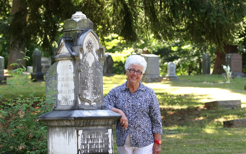 Photo Credit: OUTLOOK PHOTO: JIM CLARK - Dorothy Douglas, president of the Gresham Historical Society, pauses by a gravestone in the Gresham Pioneer Cemetery.