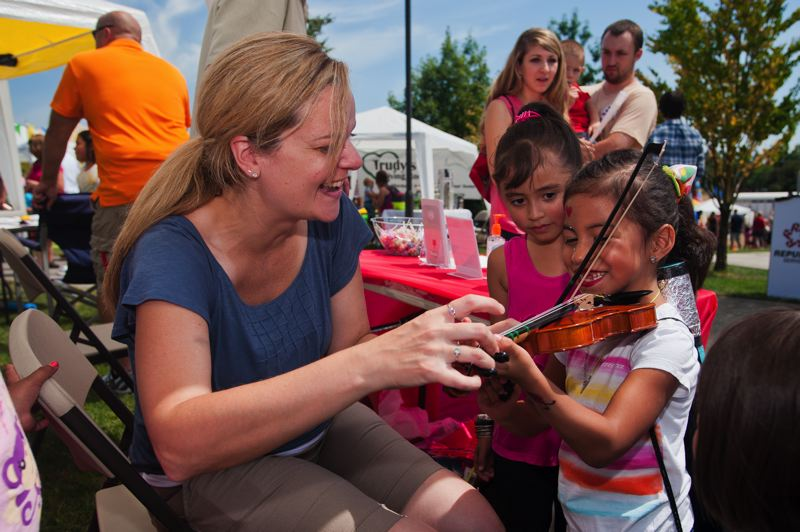 Photo Credit: SPOKESMAN FILE PHOTO - Musicman Studios is just one local business with an annual booth at Fun In The Park. Kids can sign up for music lessons or simply experience holding a violin.