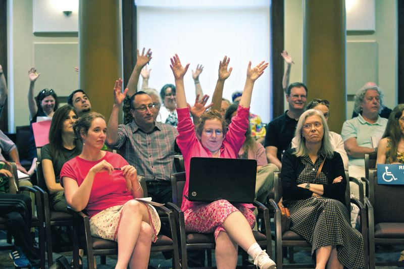 Photo Credit: TRIBUNE PHOTO JAIME VALDEZ - Portlanders waive their hands at last weeks City Council hearing to show they agree with a witness who said home demolitions are an epidemic that needs to be slowed.
