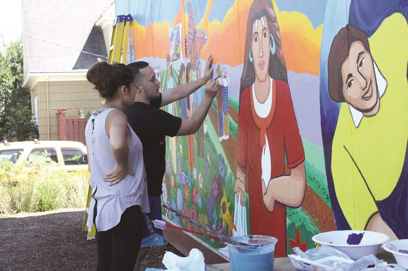 Photo Credit: TYLER FRANCKE | WOODBURN INDEPENDENT - Jasmine Garcia and Julio Solano, both volunteers from Woodburn, touch up the mural on the north wall of the Capaces Leadership Institute last week.