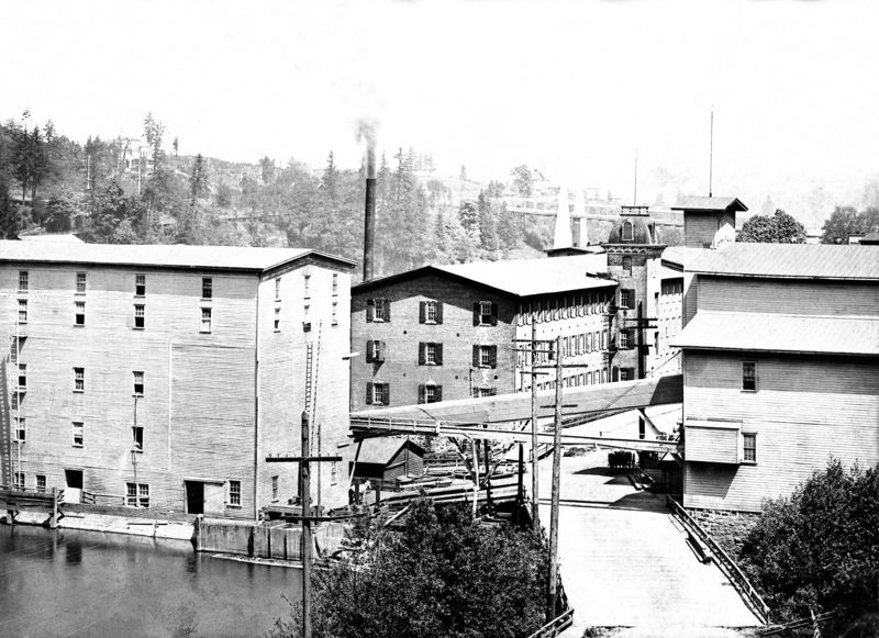 Photo Credit: PHOTO COURTESY: CLACKAMAS COUNTY HISTORICAL SOCIETY - 1890s: Newly painted Imperial Mills, warehouse, and grain elevator after the Flood of 1890. Note new covered flour conveyor inclining to top floor of warehouse, power poles from Station A, and horse drawn wagons behind Imperial Mills and in front of grain elevator.