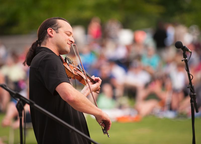 Photo Credit: SPOKESMAN PHOTO: JOSH KULLA - Violinist Aaron Meyer plays a Beatles song July 31 during a show at Wilsonville's Town Center Park.