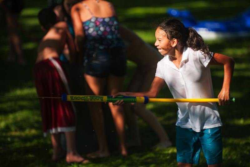 Photo Credit: SPOKESMAN PHOTO: JOSH KULLA - A girl uses an Aqua-Zooka during the Wilsonville Library's teen summer reading program water fight July 28 in Murase Plaza.