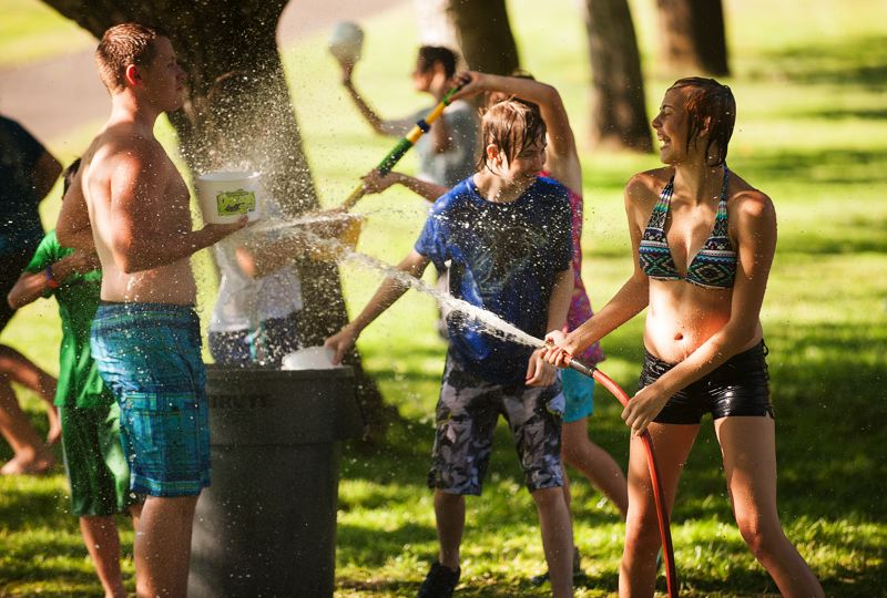 Photo Credit: SPOKESMAN PHOTO: JOSH KULLA - The Wilsonville Library's teen water fight July 28 ranged all over Murase Plaza's lower picnic area.