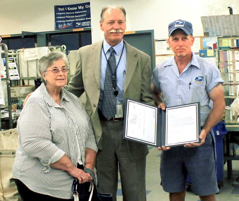 Photo Credit: NICO HAMACHER - Hero -- District Manager Kim Anderson (center) presents the USPS Postal Hero Award last week to postman Jim Styles while the woman he helped, Regina Parker, looks on.