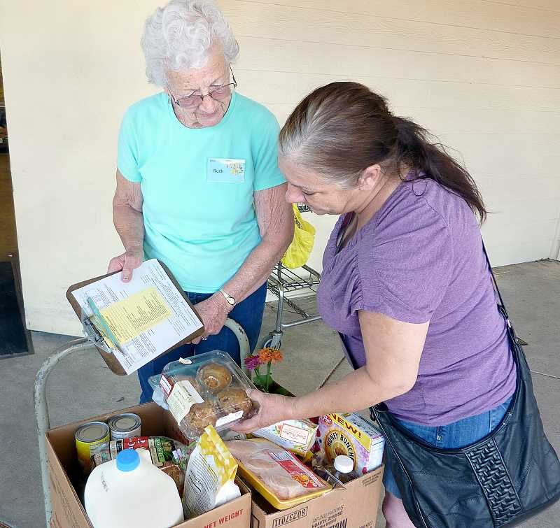 Photo Credit: SUBMITTED PHOTO - Plus one -- Volunteer Ruth Peters helps a woman collect boxes of food at Newberg F.I.S.H. The organization is adding an extra day to their schedule each month, starting Aug. 23.
