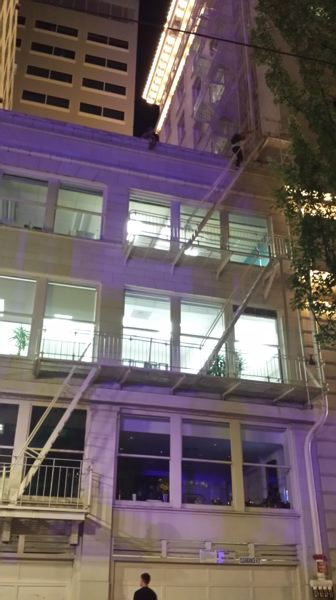 Photo Credit: JOSEPH GALLIVAN - Some of those who could not get into Pioneer Courthouse Square Tuesday evening for a free concert by Cold War Kids climbed the fire escape toget a better view from the roof of the building next to Jackson Tower.
