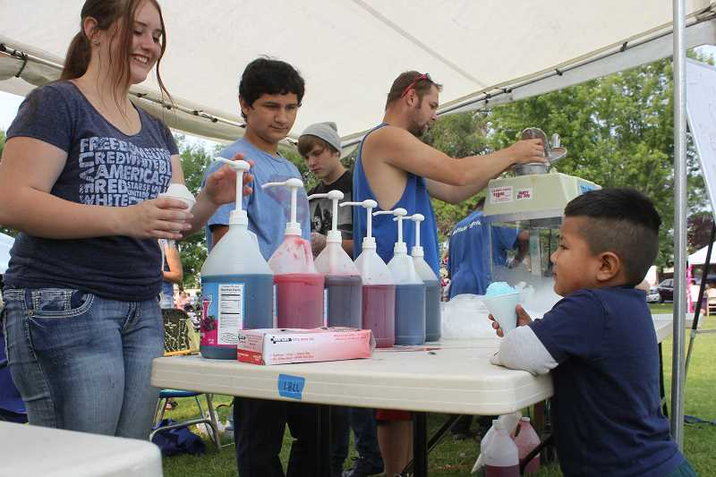 Photo Credit: SUSAN MATHENY/MADRAS PIONEER - April Claire Forman, left, hands a free SnoCone to a young boy at the Our Community event last Saturday.