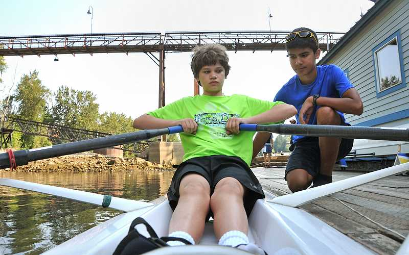 Photo Credit: TIDINGS PHOTO: VERN UYETAKE - Varsity rower Jacob Hart, right, helps novice Joe Sandmier get situated in a boat.