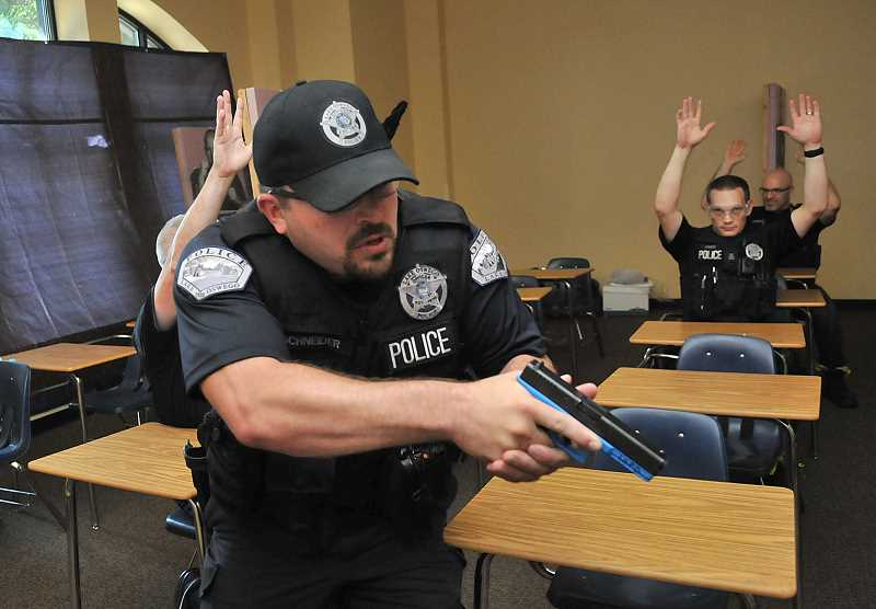 Photo Credit: REVIEW PHOTO: VERN UYETAKE - Lake Oswego Police officer Ben Schneider searches a classroom for potential gunmen during active threat exercises at Lake Oswego High School last week.