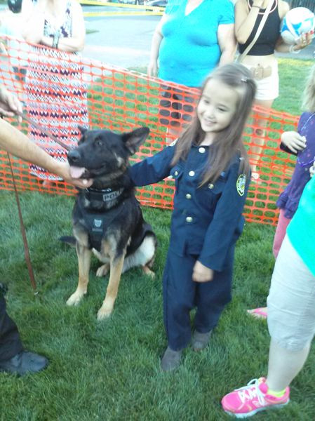 Photo Credit: TIMES PHOTO: SHANNON O. WELLS - Ella Hefty, 5, of Aloha, shares a moment with Ike, the newest black German shepherd K9 with the Beaverton Police Department, at the National Night Out event on Tuesday evening at Beaverton City Park at Southwest Fifth Street and Watson Avenue.