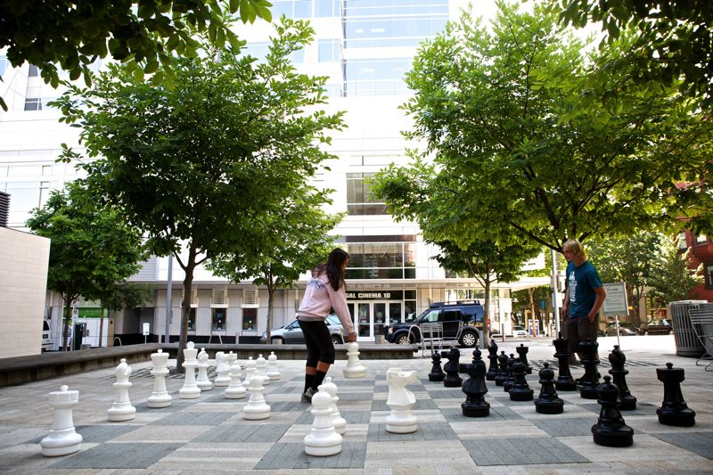 Photo Credit: TRIBUNE PHOTO: JAIME VALDEZ - Big chess (here played by Chelsea Baumgartner and Alex Pickard) is part of the programming and events that have made downtown Director Park a popular family destination. The city hopes that success can be duplicated at Holladay Park.