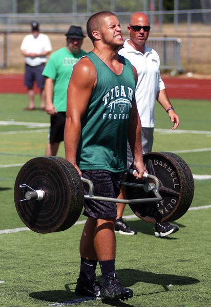 Photo Credit: DAN BROOD - CARRY IT -- Austin Goodhouse, a Tigard High School senior-to-be, competes in the farmer's carry event, walking with 315 pounds of weight.
