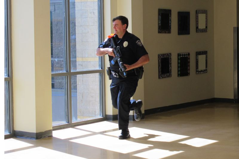 Photo Credit: HILLSBORO TRIBUNE PHOTOS: KATHY FULLER - Hillsboro Police Officer Victor Kamenir races down a hallway at Liberty High School during a drill that included securing classrooms and evacuating the school.