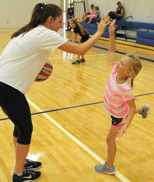 Photo Credit: LON AUSTIN/CENTRAL OREGONIAN - Makayla Lindburg, a volleyball starter for the University of Portland Pilots high five's Callie Winebarger at the Rimrock Volleyball Camp. Lindburg, who is helping at the camp, was using the high five as a teaching strategy to help teach serving.