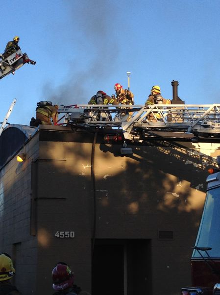 Photo Credit: SUBMITTED PHOTO: TVF&R - Tualatin Valley Fire & Rescue firefighters cut holes in the roof to ventilate the building, allowing hot gases to escape and improve visibility inside the building. Once ventilation was complete, crews re-entered the building to extinguish the remaining fire.