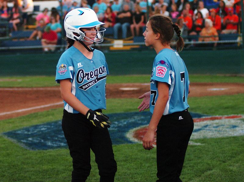 Photo Credit: DAN BROOD - NICE TRY -- Tigard/TC's Carly Atwood (right) greets teammate Alexis Klum following the final play of Friday's game at the Little League Softball World Series.