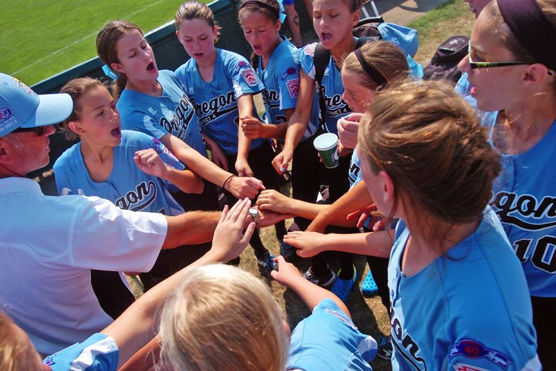 Photo Credit: DAN BROOD - BE LOUD -- The Tigard/Tualatin City players and coaches put their hands in following the win Sunday at the Little League Softball World Series.
