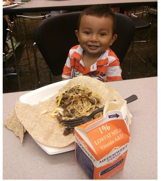 Photo Credit: COURTESY OF PARTNERS FOR A HUNGER-FREE OREGON - A child enjoys a meal at the Rockwood Library branch through the summer food program aided in part by the Partners for a Hunger-free Oregon.
