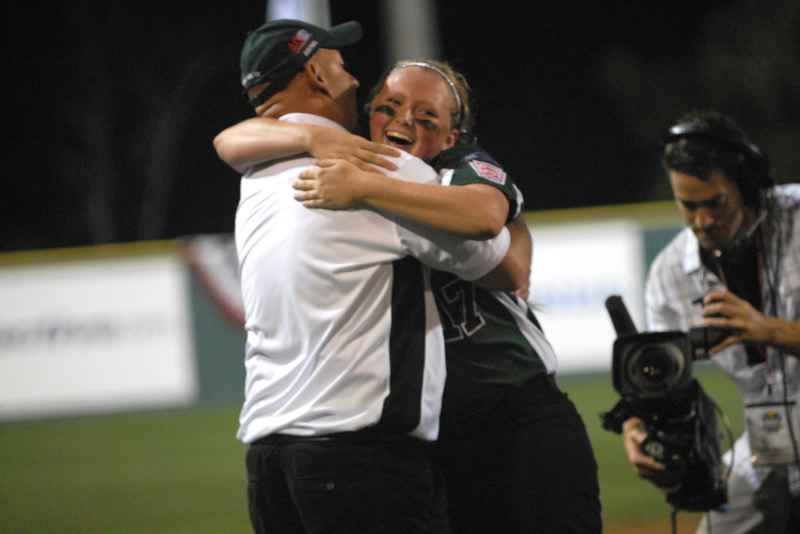 Photo Credit: PORTLAND TRIBUNE: DAVID BALL - Tallmedge pitcher Emily Pratt embraces manager Nick Dadich after her team recorded the final out in Mondays 4-1 win over Puerto Rico.