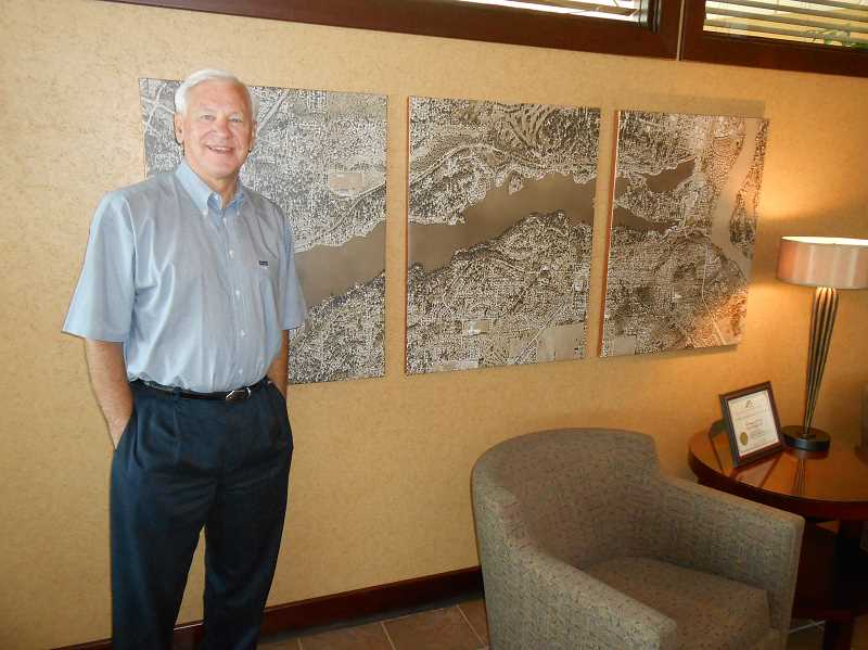 Photo Credit: REVIEW PHOTO: CLIFF NEWELL - Dan Heine stands in front of a map of Lake Oswego at his bank on State Street. His contributions to community life earned him many awards.