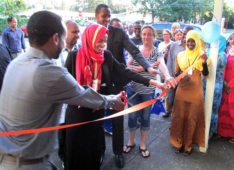 Photo Credit: OUTLOOK PHOTO: LAURA KNUDSON - Jamal Dar, executive director of AYCO, invites community members to participate in the ribbon cutting, marking the opening of its new office. The new location will better serve East Multnomah County refugee families.