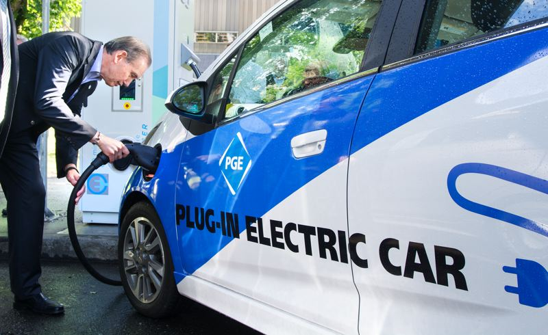 Photo Credit: TRIBUNE PHOTO JOHN M. VINCENT - Charlie Allcock, Director of Business Development for Portland General Electric plugs the new SAE Combo fast charger in to a Chevrolet Spark EV during a press event at Portland State University's Electric Avenue.