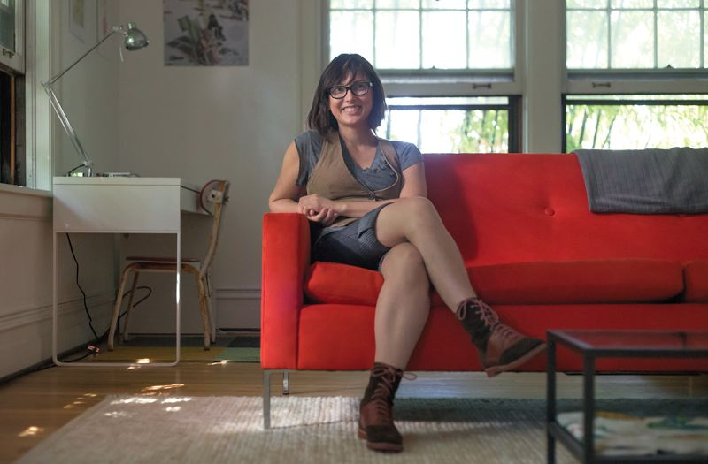 Photo Credit: TRIBUNE PHOTO: JONATHAN HOUSE - Melissa Toman on the couch she reupholstered for Airbnb guests who take her studio for $108 a night.