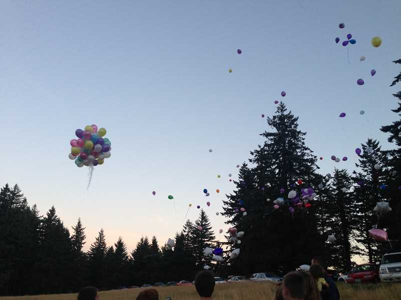 Photo Credit: JANIE WHITE - Students launch balloons in memory of Sabrina Baxter on Aug. 8 at Bald Peak Park, one of Sabrina's favorite places.