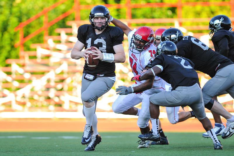 Photo Credit: PHOTO BY JOHN LARIVIERE - Russell Schneider (13), pictured here eluding a defender in a Pacific Football League playoff game with the Yakima Mavericks, will be at the helm for the Oregon City High School alumni team for this Saturday's Oregon City vs. West Linn Battle for the Bridge alumni football game. Schneider has had a phenomenal year as quarterback for the Oregon City-based Portland Raiders Minor League semi-pro football team this year. The 2001 graduate of Oregon City High School was in record form, completing 267-of-490 passes (.544 percent) for 4,419 yards and 57 touchdowns, with 17 interceptions. The passes completed, passes attempted and yards are all PFL and Greater Northwest Football Association records. The 57 touchdown passes is second all-time only to his own record of 59. Schneider has 370 career touchdown passes in six seasons of playing Minor League semi-pro football, just seven shy of the national record. Schneider this year led the Raiders to championship of the Pacific Football League, and an overall record of 12-1, the Raiders' only loss coming in a 10-7 early-season game with the South Lane Buzzards.