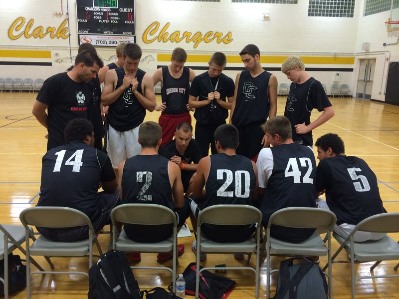 Photo Credit: PHOTO BY CHRIS MENGIS SR. - Oregon City coach Aaron Newkirk maps out strategies during a Las Vegas Tournament game played at Clark High School. Pictured are: (seated, left to right) Chris Mengis, Briggs Young, Mason Martin, Austin DeWitz and Teron Bradford; and (standing) assistant coach Bryce Fisher, Chase Kaloust, Tanner Fowler, Jake Sather, Austin Sillett, Jake Vetter, Ben Sisul and Chris Figert.