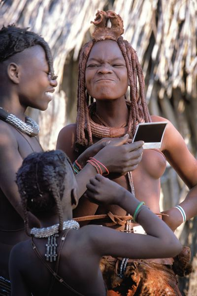 Photo Credit: PHOTO COURTESY OF JANIS MIGLAVS - While this is the first time she's seen a photo of herself, this Himba tribesgirl's reaction is not unlike that of an American girl looking at a selfie.