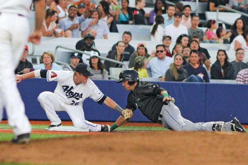 Photo Credit: HILLSBORO TRIBUNE PHOTO: CHASE ALLGOOD - Hillsboro third baseman Nate Robertson lays a tag on Eugene's Nick Torres on a stolen base attempt during last Friday's Northwest League baseball game at Ron Tonkin Field.