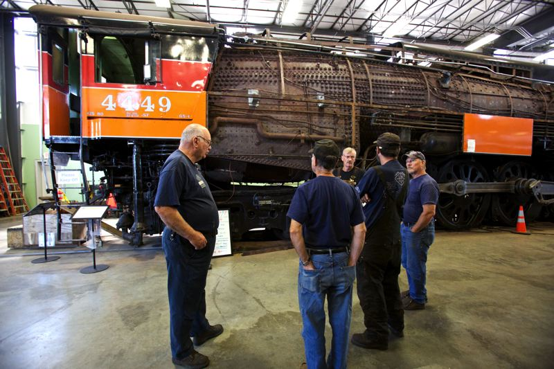 Photo Credit: TIMES PHOTO: JAIME VALDEZ - Doyle McCormack, left, engineer of the SP 4449 and president of the Oregon Rail Heritage Center, talks with other volunteers about their next tasks.