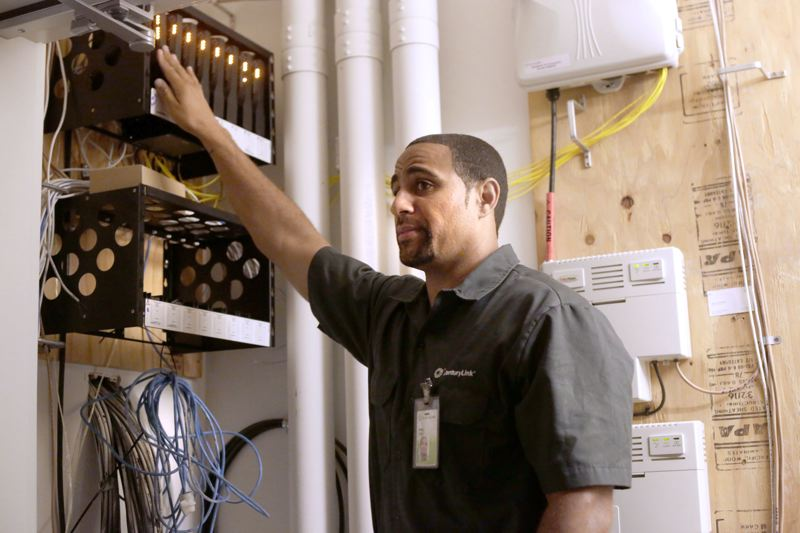 Photo Credit: TRIBUNE PHOTO: JONATHAN HOUSE - CenturyLink technician Willie Mays explains the company's 1 gigabit service equipment in the new Burnside 26 apartments.