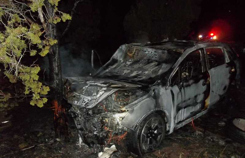 Photo Credit: CONTRIBUTED PHOTO - This 2014 Subaru Crosstrack became fully engulfed in flames after hitting a Nissan that was blocking the road, leaving the highway and striking a juniper tree.