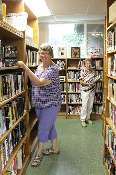 Photo Credit: LINDSAY KEEFER - Josie Hyde (left) and Jan Metzger work on filling the shelves of the newly opened North Marion Community Library, located in the basement of Aurora Presbyterian Church. The library will have its grand opening from 10 a.m. to 2 p.m. Saturday.