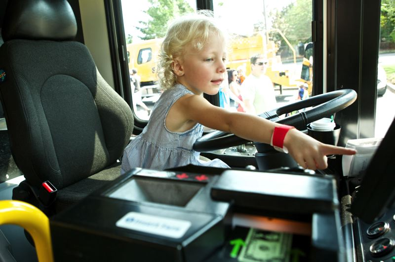 Photo Credit: TIMES PHOTO: JAIME VALDEZ - Charlotte Happel, 4, of Beaverton works the controls of a TriMet bus on display during the family-friendly event.