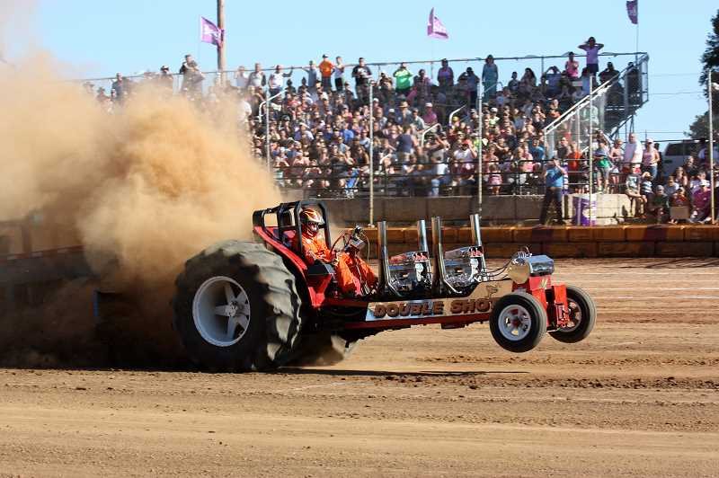 During Sundays tractor pull event at Sunset Speedway in Banks, the customized Double Shot tractor bounces into the air as it struggles to move a heavy sled.