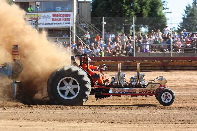 Photo Credit: HILLSBORO TRIBUNE PHOTO: DOUG BURKHARDT - Action was hot and dusty Sunday with the annual Banks BBQ Truck & Tractor Pull and the Combine Demolition Derby in full swing at Sunset Speedway. Here, a customized tractor, Double Shot, bounces into the air as it struggles to move a heavy sled during tractor pull events Sunday.